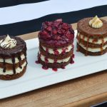 Three layer sheet pan mini cakes filled with white chocolate whipped cream frosting. Each with different toppings, chocolate fudge, seasonal fruit compote, and caramel respectively. All on a white platter