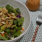 bowl of mixed greens salad with crunchy almond and ramen topping next to a fork and dressing carafe.