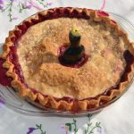 Mixed berry pie with golden crust in a clear glass pie pan and a pie bird in the center.