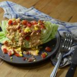 A large wedge of crisp iceberg lettuce, layered in thousand island dressing with egg and relish.