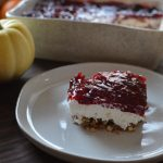Plated pretzel-crusted cheesecake topped with whole cranberry sauce