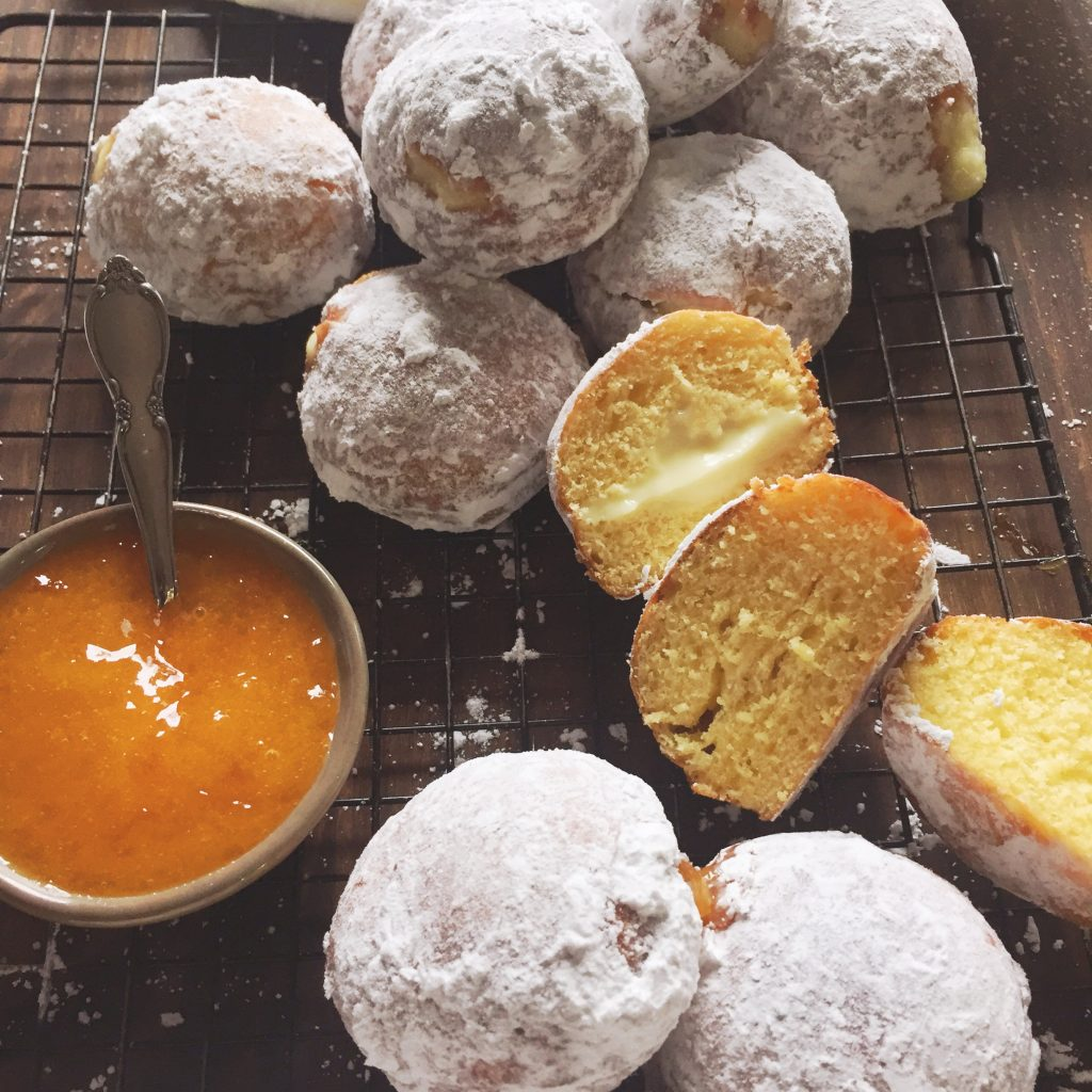 Powdered sugar coated paczki filled with custard next to a bowl of blended apricot filling.