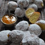 A mound of freshly baked paczki, coated in powdered sugar with fresh apricot filling.