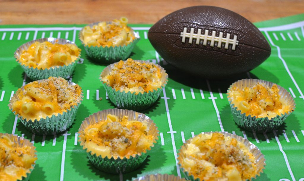 Mac and Cheese cups on a football field placemat, next to a toy football.