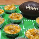 Mac and Cheese cups on a football field placemat next to a toy football.