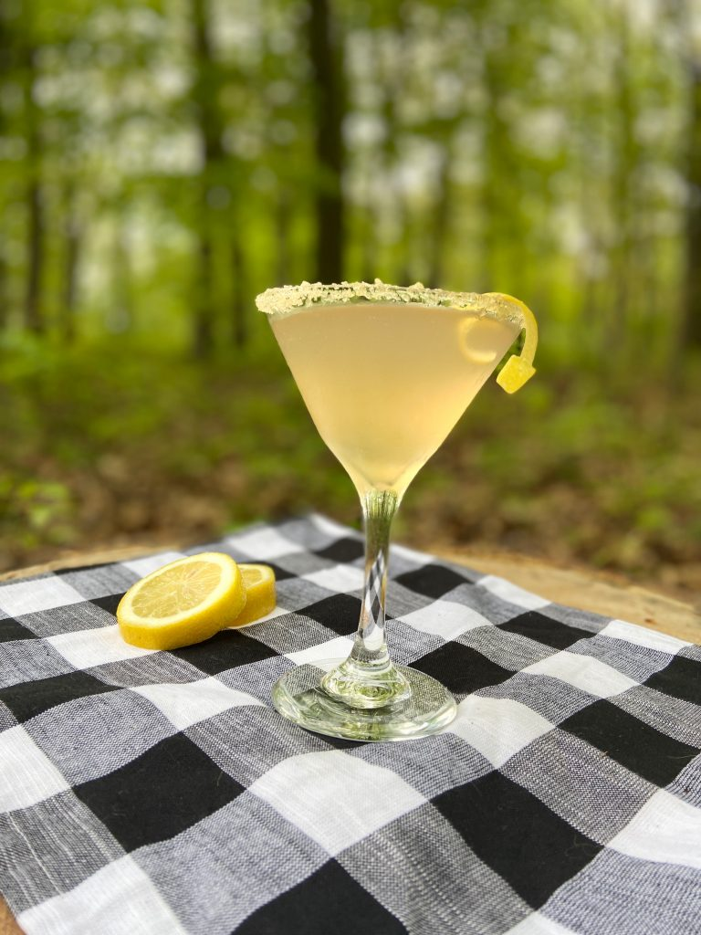 A French 75 in a martini glass with brown sugar on the rim and a lemon twist.