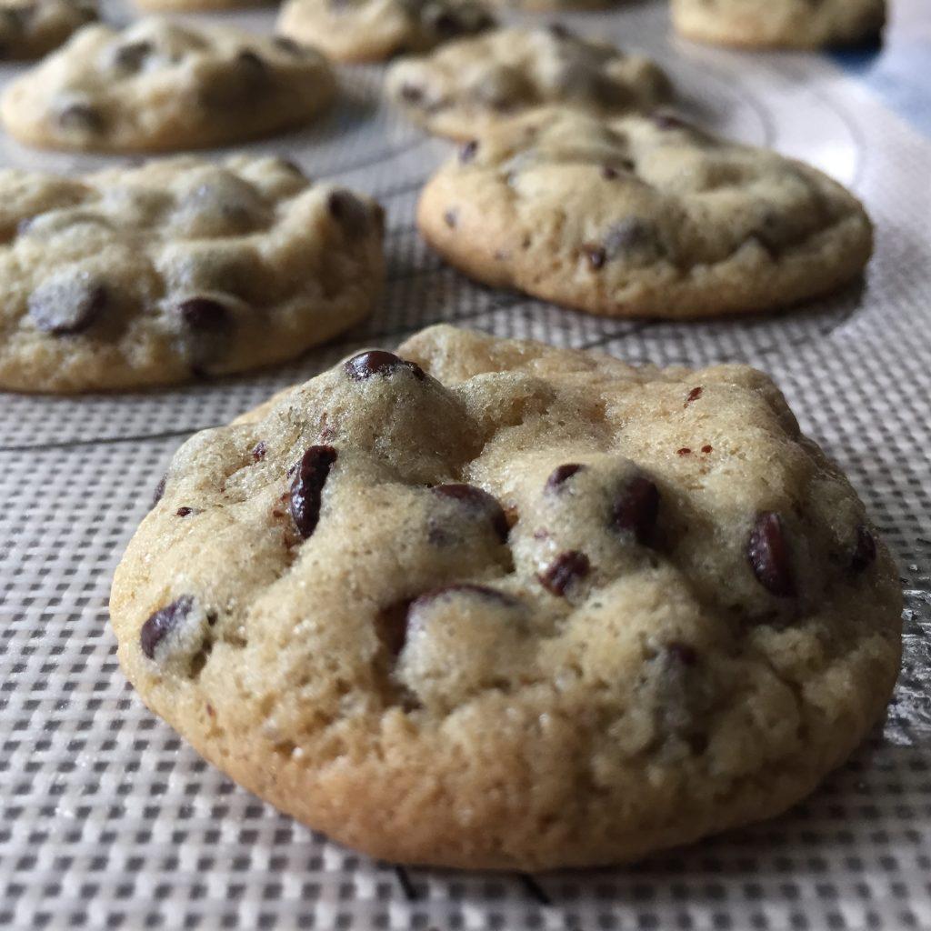Fresh chocolate chip cookies cooling on a baking matt.