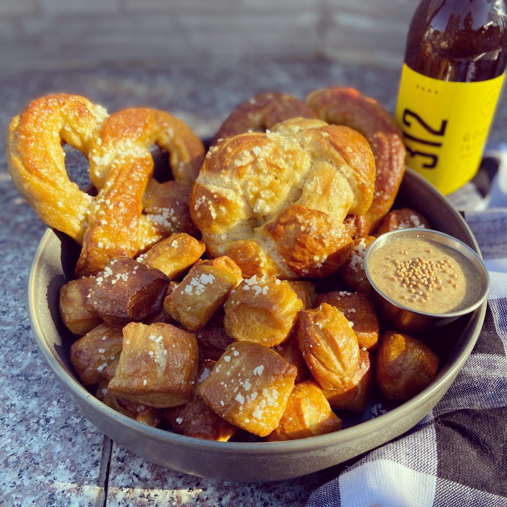 A large ceramic bowl filled with a mix of sourdough pretzel bites and large soft pretzels.  A cup of dipping mustard sits atop the pretzels.