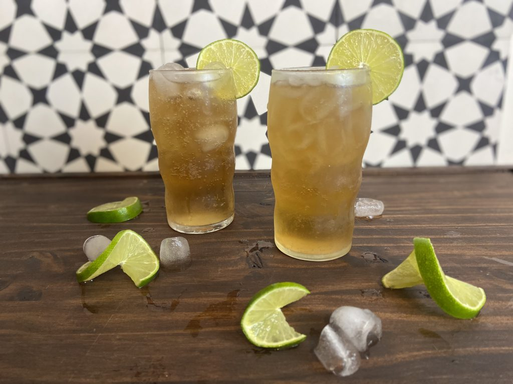Two tall glasses of Dark and Stormy cocktails with fresh lime wedges.