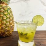 A rocks glass with a pineapple rum smash, garnished with a lime.