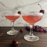 Two glasses of pink lady cocktails, garnished with fresh cherries