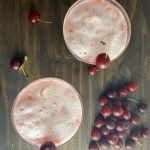 Two frothy pink ladies with fresh cherries