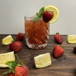 A whisky and strawberry kombucha smash in a rocks glass, garnished with a strawberry and lemon wedge.