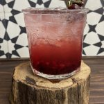 A rocks glass filled with a cherry gin and jam